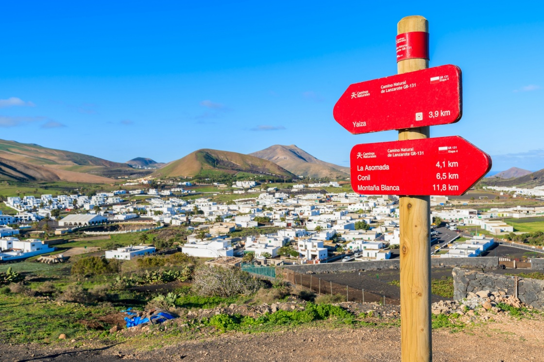 In focus trekking sign with blurred Uga village in background, Lanzarote, Canary Islands, Spain